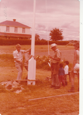 Alan la Roche and Arthur White erecting the flagpole in Howick Historical Village.; c1979; P2021.114.02
