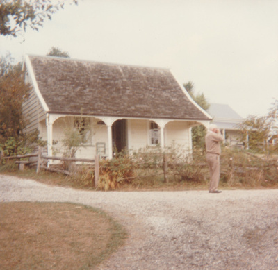 A man taking a photograph on the path outside Sergeant Barry's cottage in Howick Historical Village. ; P2020.140.01