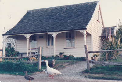 A goose and duck are walking past Sergeant Barry's cottage in Howick Historical Village. ; P2020.129.04
