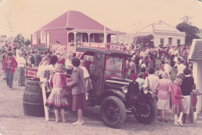 A vintage car surrounded by people in Howick Historical Village. De Quincey's and Johnson's cottages are in the background.; La Roche, Alan; 11 October 1981; P2021.108.15