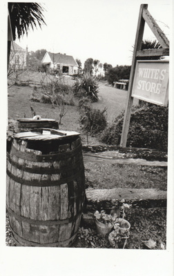 Looking across grass to the Forge showing a White's Store sign and a barrel.; Eastern Courier; 19 February 1992; P2020.75.01