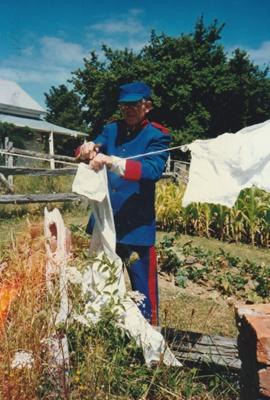 Alan la Roche in Fencible uniform, pegging out washing in Howick Historical Village.; La Roche, Alan; P2021.118.28