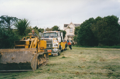 A Truck towing heavy vehicle following a bulldozer clearing the way for moving half of Puhinui to its new site in the Howick Historical Village. ; Smith, Malcolm; May 2002; P2020.16.05