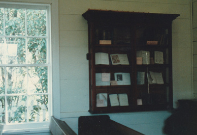 A cabinet on the wall of the Howick Methodist Church at the Howick Historical Village, containing books. ; November 1989; P2020.40.05