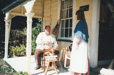 Grant Christianson, working as a bodger on a pole lathe on the verandah of Sergeant Barry's cottage with a volunteer in costume, on a Live Day at Howick Historical Village.; La Roche, Alan; P2021.87.03