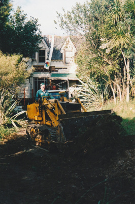 A bulldozer, showing the driver, preparing the way for a Johnson's Heavy truck and trailer to move Puhinui to its new site in the Howick Historical Village.; Alan La Roche; May 2002; P2020.11.31