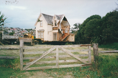 Half of Puhinui on its new site in the Howick Historical Village. A bulldozer and truck are to the side, a fence and gate in the foreground.; Smith, Malcolm; May 2002; P2020.16.19