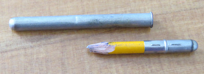 Silver holder with a well used pencil inserted. Pa...