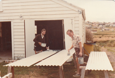 Jim and David Edwards painting the roofing iron for the Coachhouse in the Howick Historical Village. ; La Roche, Alan; 26 february 1983; P2021.24.01
