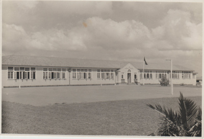 Howick District High School with a flag flying o the flagpole.; Sloan, Ralph S; 1950s; 2019.079.01