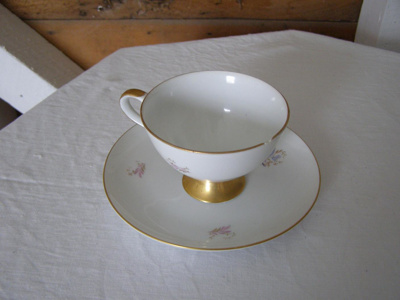 White ceramic tea cup and saucer with gold rim and...