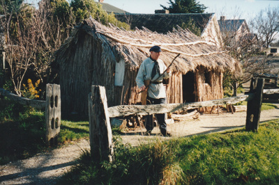 A volunteer in costume in front of the mail runner's cottage. ; La Roche, Alan; P2021.83.15