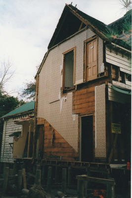 Half of Puhinui awaiting removal to its new site in the Howick Historical Village. ; Smith, Malcolm; May 2002; P2020.16.16