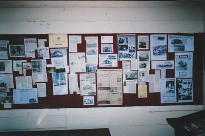 A display of photographs and newspaper items depicting the years 1962-2002, in Brindle Cottage in the Howick Historical Village. ; La Roche, Alan; 2002; P2021.41.01