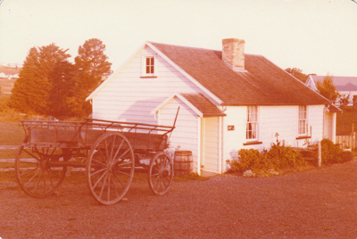 A cart outside Briody-McDaniel's cottage, previously McDermott's, at the Howick Historical Village.; March 1981; P2020.98.27