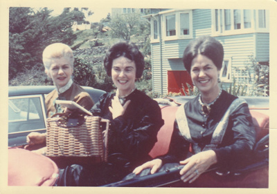 Dee Collings, Alywn Zellman and Eileen Martensen, all in costume at the November 1965 re-enactment of the Fencible landing in 1847. Shown seated in an open topped car in front of a house at Howick beach.; November 1965; P2021.91.22