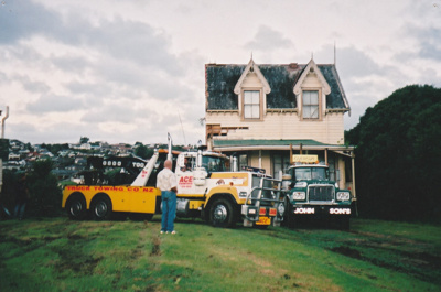 A man is standing in fron of an Ace Towing Co. and a Johnson's truck in front of Puhinui on its new site in the Howick Historical Village. ; Alan La Roche; May 2002; P2020.11.24