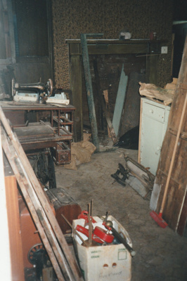 Puhinui kitchen before restoration, showing the fireplace, cabinets, a Singer sewing machine, a broom and sundry tools and materials.; Alan La Roche; 2002; P2020.14.25