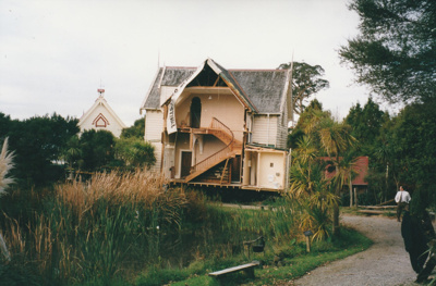 Half of Puhinui being moved to its new site in the Howick Historical Village. Pakuranga School and the Dame school are in the background; the pond in the foreground.; Smith, Malcolm; May 2002; P2020.16.10
