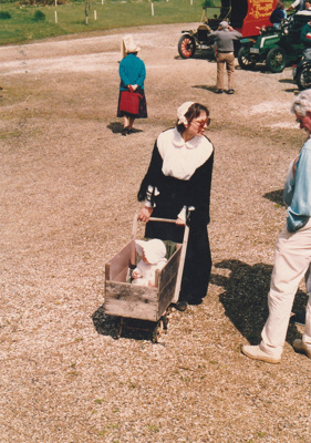 Barbara Doughty, from the Education Dept. in costume pushing a baby in a pushcahair made from a box.; P2021.105.06