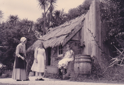 A lady and 2 girls in costume outside the Sod Cottage, Howick Historical Village on a Live Day.; La Roche, Alan; P2020.45.01
