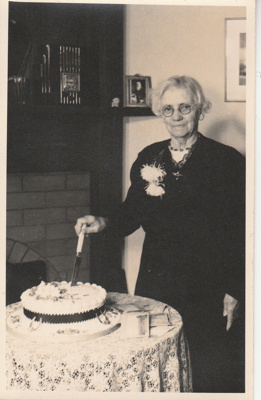 Martha Hattaway, 1852-1915, on her 80th birthday cutting the cake.; Ikonta Studios, Queen St. Auckland; 14 May 1947; P2021.163.07