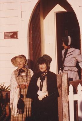 Three ladies in costume leaving the Howick Methodist Church.; 1985; P2020.35.01