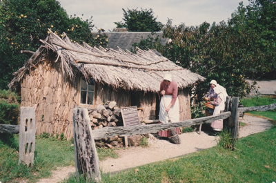 Tracy Mulgrew in costume sweeping the path in front of the Sod Cottage, Howick Historical Village on a Live Day. Brenda Scott and her granddaughter are on the right.  ; La Roche, Alan; P2020.43.33