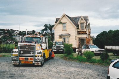 A Truck Towing  and a Johnson's truck moving away after delivering half of Puhinui onto its new site in the Howick Historical Village.; Alan La Roche; May 2002; P2020.11.17