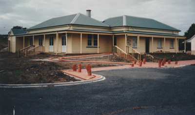 Front view of White's Homestead at Howick Historical Village, showing the paved parking area and brick path being laid.; McKinley, Stuart; 1996; P2021.72.01