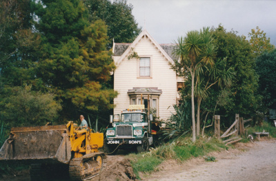 A bulldozer preparing the way for a Johnson's Heavy truck and trailer to move Puhinui to its new site in the Howick Historical Village.; Smith, Malcolm; May 2002; P2020.16.01