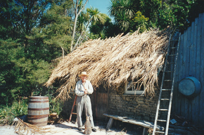 Alan la Roche with a broom outside the sod cottage in Howick Historical Village. ; P2021.118.12