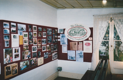 A display of photographs and newspaper items depicting the years 1962-2002, in Brindle Cottage in the Howick Historical Village. ; La Roche, Alan; 2002; P2021.41.04