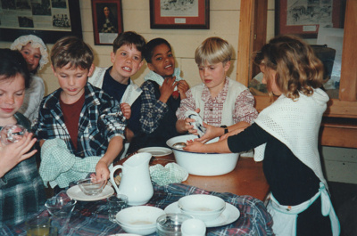 """Children doing the dishes after a 'sleepover"""" holiday programme in Pakuranga School in the Howick Historical Village.; P2020.66.03"""