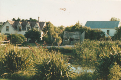 View across the pond showing Puhinui, the sod cottage and the Howick Methodist Church at the Howick Historical Village.; 1989; P2020.50.01