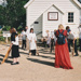 School children and a teacher stilt walking in Howick Historical Village.; La Roche, Alan; P2021.125.01