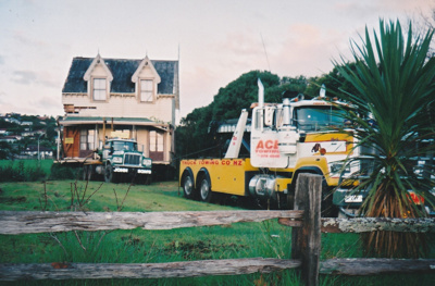Ace Towing Co. and a Johnson's truck leaving Puhinui on its new site in the Howick Historical Village. ; Alan La Roche; May 2002; P2020.11.25
