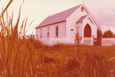 Front and side view of the Howick Methodist Church in the Howick Historical Village, looking across the grass.; December 1980; P2020.34.09