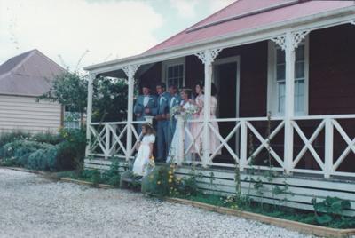 The Cossey wedding party on the verandah of de Quiney's cottage in Howick Historical Village. ; Millen, Marcia; 199?; P2021.130.02