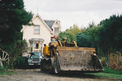 A bulldozer, showing the driver, preparing the way for a Johnson's Heavy truck and trailer to move Puhinui to its new site in the Howick Historical Village.; Alan La Roche; May 2002; P2020.11.29