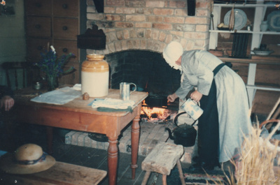 A guide in costume tending tor the fire in Michael Ford's cottage, in the Howick Historical Village. ; La Roche, Alan; 2004; P2021.49.10