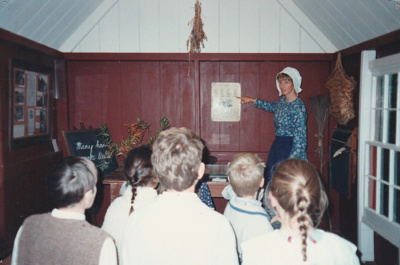 Children and a teacher, in costume, in the Dame School at Howick Historical Village.; 1995; P2021.59.01