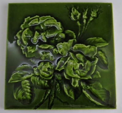 Glazed ceramic tile, with rose pattern in relief. ...