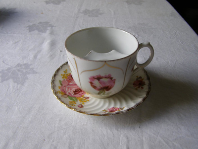 Ceramic tea cup with pink roses and gold detail an...