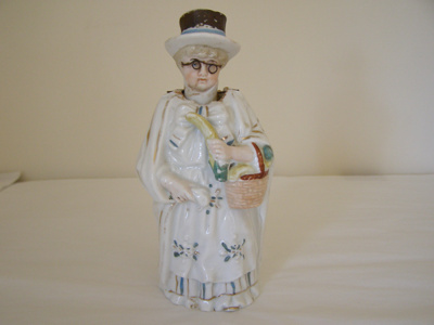 Ceramic ornament, a nodding lady, holding a bask...