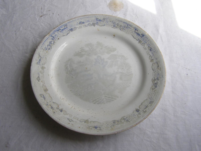 Ceramic bread plate with faded blue willow design.