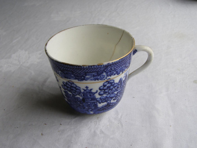 Ceramic teacup with blue willow design and gold ed...