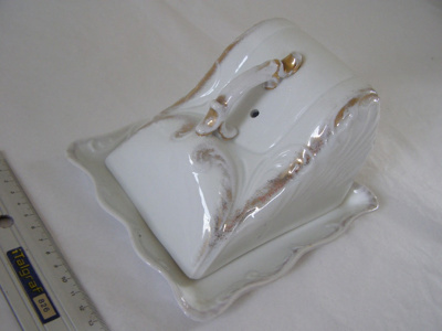 White ceramic cheese dish with gold accents.