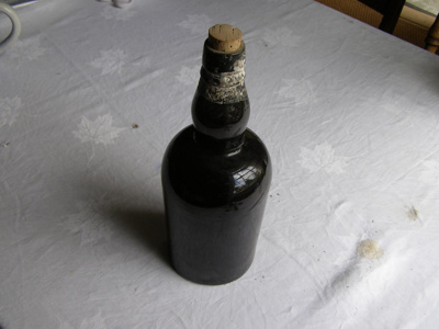 dark green/black glass bottle with cork stopper.