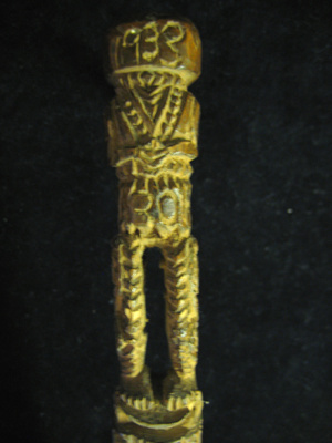 Carved wooden walking stick with figure at the top...